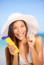Sunscreen woman applying suntan lotion laughing beautiful vivacious in a sunhat and bikini cream Stock Photo