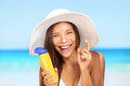 Sunscreen woman applying suntan lotion showing bottle beautiful smiling happy asian with cream in plastic container Royalty Free Stock Photography