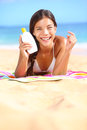 Sunscreen woman showing suntan lotion bottle applying solar cream to nose beautiful smiling happy asian with cream in Stock Images