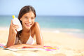 Sunscreen woman showing suntan lotion bottle beautiful smiling happy asian with cream in plastic container lying on Royalty Free Stock Images