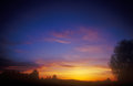 Sunset beautiful multicolored over a dark landscape Royalty Free Stock Image