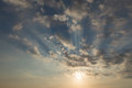 Sunset on a blue sky with sun rays and clouds Stock Image