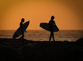 Sunset boards kids going surf on the walking on rocks Stock Photos