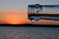Sunset and a bottle picture of through the tip of wine in mozambique only the tip is in focus but the droplets give it bit of Royalty Free Stock Image