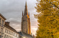Sunset from bruge fall is the best season in belgium yellow leaves left remark on the church Stock Photo