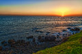 Sunset on a calm sea with a green grass and rocks Royalty Free Stock Photo