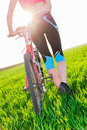 Sunset close up of woman walking along bike back view closeup young riding bicycle outside in the and green grass field Royalty Free Stock Images