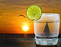 Sunset cocktail with sailboat lime garnish and background Royalty Free Stock Photography