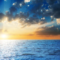 Sunset in dark sky over blue sea Royalty Free Stock Photo