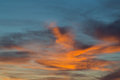 Sunset in dramatic blue sky with clouds in orange color tones Royalty Free Stock Photo