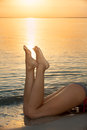 Sunset feet of young woman on beach at Stock Image