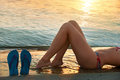 Sunset feet of young woman on beach at Royalty Free Stock Photo