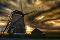 Sunset house and the giant of netherlands over a beautiful little guarded by windmill Royalty Free Stock Images