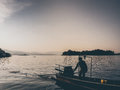 Sunset lake and silhouette of man and motor boat. Royalty Free Stock Photo