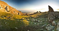 Sunset in mountains and rocks above the sea panorama of with grass on hill Stock Images