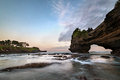 Sunset near famous tourist landmark of Bali island - Tanah Lot & Batu Bolong temple. Royalty Free Stock Photo