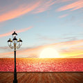 Sunset ocean scenery with wooden boardwalk and lantern romantic Stock Photos