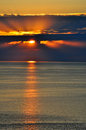 Sunset over the black sea sochi dark clouds behind which hid sun and solar path on calm water Stock Photography