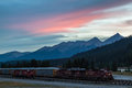Sunset over canadian rockies with an idle train in field british columbia canada Royalty Free Stock Images