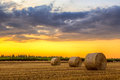 Sunset over farm field with hay bales Royalty Free Stock Photo