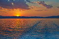 Sunset over the greece waves from the ferry and mediterranean sea sun sets behind mountains on horizon Royalty Free Stock Photography