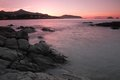 Sunset over ile rousse in corsica pink the balagne region of with rocks and the sea the foreground Royalty Free Stock Image