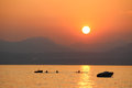 Sunset over lake garda in italy from bardelino view the harbor area of looking across past some rowers and other small boats to Royalty Free Stock Images