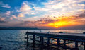 Sunset over a pier sun sets into the clouds sea on foreground Stock Images