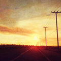 Sunset over road with telegraph poles country scene Royalty Free Stock Photo