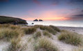 Sunset over sand dunes on the cornwall coastline beautiful holywell bay near newquay in Stock Photography