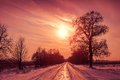 Sunset over snowy road Royalty Free Stock Photo