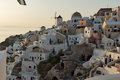 Sunset over white windmills in  town of Oia and panorama to Santorini island, Thira, Greece Royalty Free Stock Photo