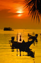 Sunset with palm and boats on tropical beach Royalty Free Stock Photo