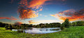 Sunset at the park a beautiful view of a with a pond under a vibrant cloudy sky Stock Photo