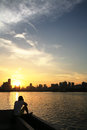 Sunset of riverside male figure sitting on the zhujiang riverbank in front the yellow in guangzhou china hi is taking photo Royalty Free Stock Photos