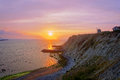 Sunset on the sea with aixerrota mill and pink colors Stock Photo