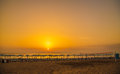 Sunset on the sea beach with sun loungers parasols and a volley volleyball court Royalty Free Stock Image