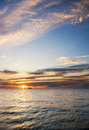 Sunset on the sea cargo ship sailing away against colorful Royalty Free Stock Images