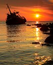 Sunset at sea, the sun sets over the horizon. The ship is stranded, the sun`s rays are reflected in the water Royalty Free Stock Photo