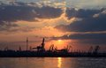 Sunset with silhouettes of cargo cranes in odessa port black sea ukraine Stock Photos