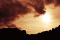 Sunset sky with dark clouds and sun shining over mountains Royalty Free Stock Photography