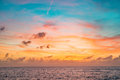 Sunset sky in red and blue color with subtle clouds over the sea horizon Royalty Free Stock Photo