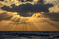 Sunset with sun beams over the sea Royalty Free Stock Photo