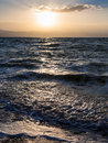 Sunset and surf at Dead Sea in winter dusk Royalty Free Stock Photo