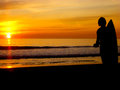 Sunset with surfer on a beach at the end of the sea coming back to the resting peacefully and he take moment to admire the beauty Royalty Free Stock Image