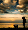 Sunset times woman tourist with a dog on the shore of beautiful lake Royalty Free Stock Images