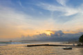 Sunset on a tropical sea shore with breakwaters and boats bali in candidasa indonesia Stock Photos