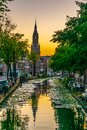 Sunset view of Niuewe Kerk church behind a channel in Delft, Netherlands Royalty Free Stock Photo