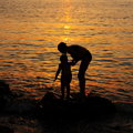 Sunset wallpaper mother and child stock pictures silhouettes against sun light on evening sea background Royalty Free Stock Photo