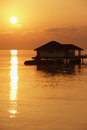 Sunset and a water bungalow in the Indian Ocean Stock Images